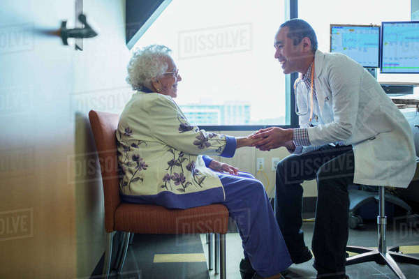 Smiling male doctor holding hand while talking to patient in hospital ward Royalty-free stock photo