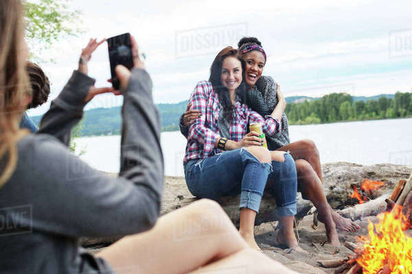 Woman photographing happy female friends sitting on tree trunk by campfire against river Royalty-free stock photo