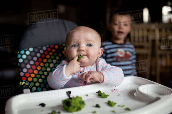 Baby girl eating food on high chair while brother standing in background Royalty-free stock photo