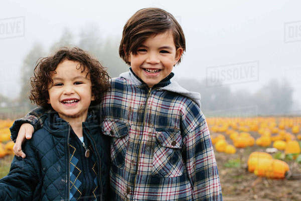 Portrait of happy brothers standing at pumpkin patch during foggy weather Royalty-free stock photo