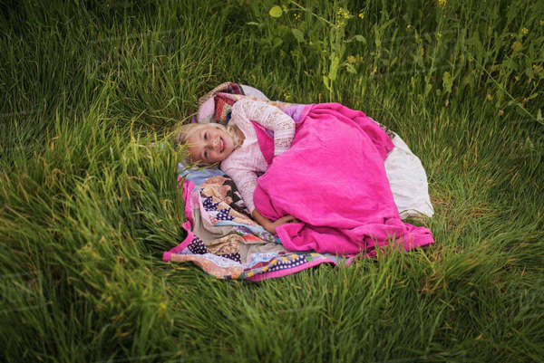 High angle portrait of happy girl lying on blanket amidst grassy field Royalty-free stock photo