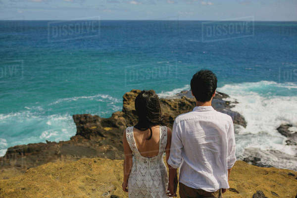 Rear view of couple holding hands and standing at beach against sky Royalty-free stock photo