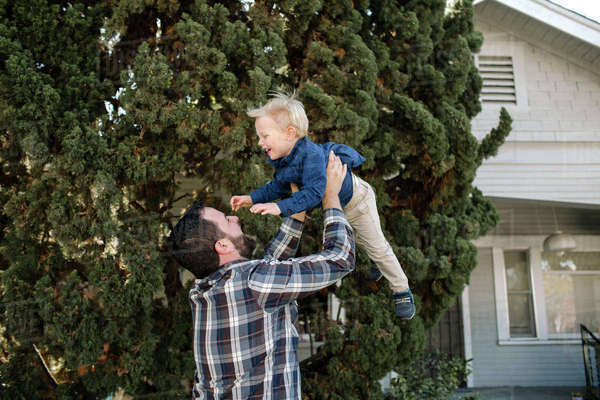 Father picking up son while standing by tree at backyard Royalty-free stock photo