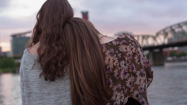 Handheld shot of female friends looking at view while standing by Willamette River during sunset Royalty-free stock video