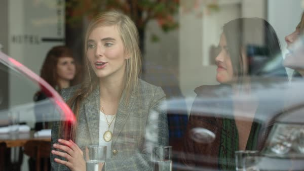 Handheld shot of friends talking in restaurant seen through window Royalty-free stock video
