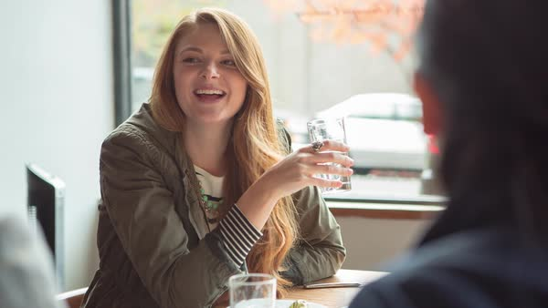 Handheld shot of woman holding drinking glass while talking with friends in restaurant Royalty-free stock video