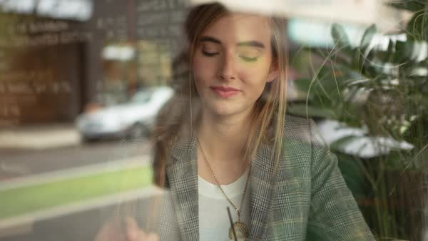 Handheld shot of happy woman in restaurant seen through window Royalty-free stock video
