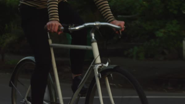 Handheld shot of woman cycling on road Royalty-free stock video
