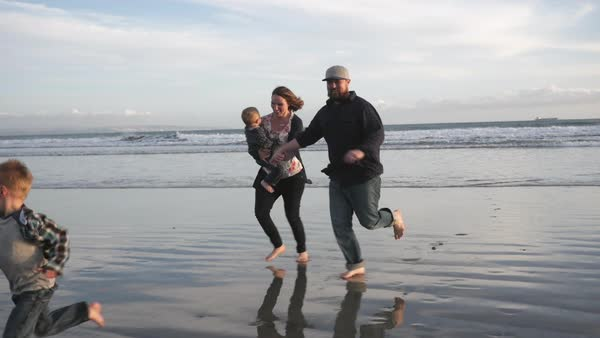 Handheld shot of happy family running on shore at beach Royalty-free stock video