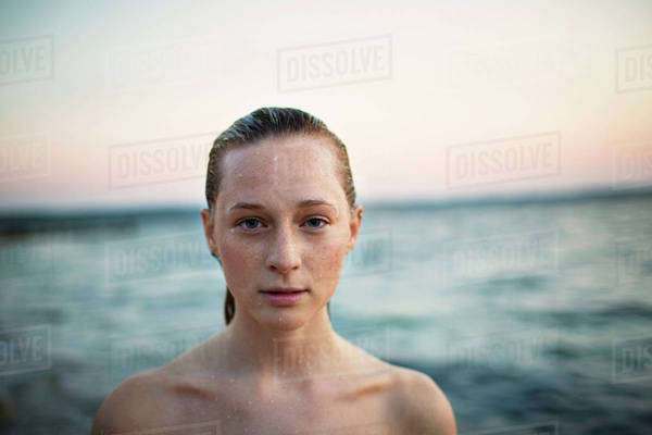 Portrait of young woman by sea at sunset Royalty-free stock photo
