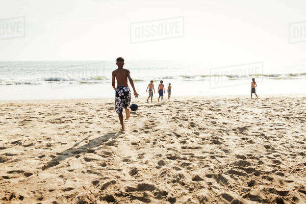 Boys (10-11, 12-13) playing soccer at beach Royalty-free stock photo