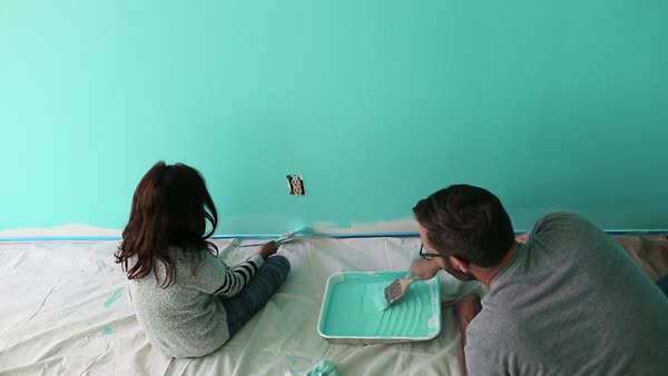 Handheld shot of father and daughter painting wall at home Royalty-free stock video