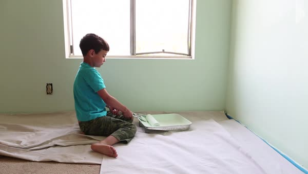 Handheld shot of boy using paint roller while painting wall at home Royalty-free stock video
