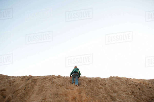 Rear view of boy climbing on sand dune at beach against sky Royalty-free stock photo