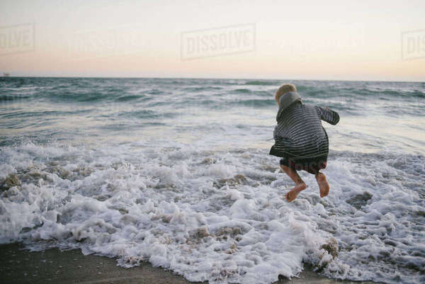 Rear view of boy jumping on shore at beach against sky Royalty-free stock photo