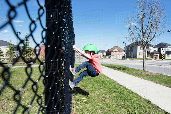 Side view of boy climbing on chainlink fence at park Royalty-free stock photo
