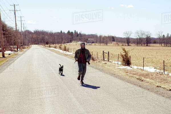 Full length of man and dog running on country road during vacation Royalty-free stock photo