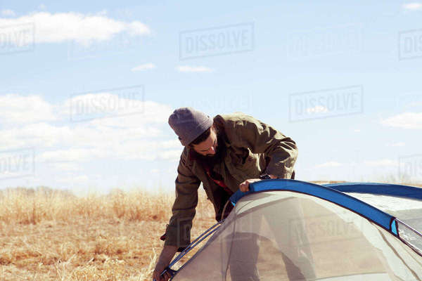 Man setting tent on field against sky Royalty-free stock photo