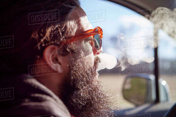 Side view of male hipster smoking in car during vacation Royalty-free stock photo
