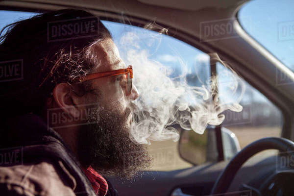 Side view of hipster smoking in car during vacation Royalty-free stock photo