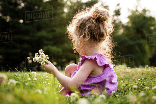 Side view of girl picking flowers while sitting amidst field at park Royalty-free stock photo