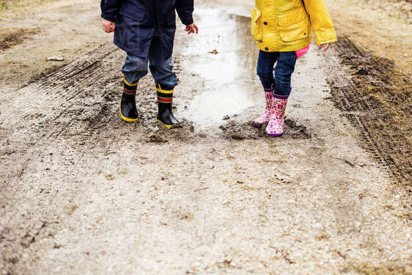 Low section of siblings playing in muddy puddle Royalty-free stock photo