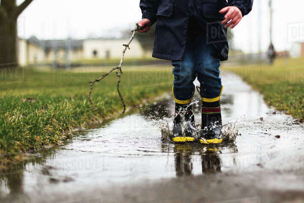 Low section of boy holding stick while jumping in puddle Royalty-free stock photo