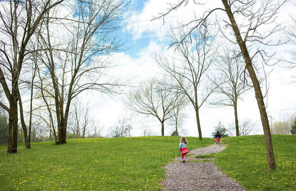 Rear view of siblings walking on footpath against cloudy sky at park Royalty-free stock photo