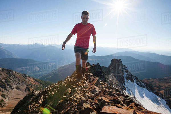 Male hiker walking on rocky mountains against sky during sunny day Royalty-free stock photo