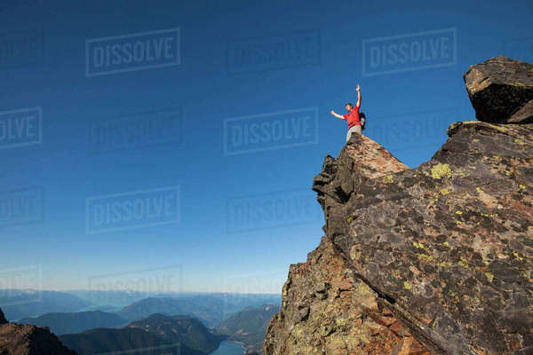 Low angle view of hiker with arms raised standing on rocky mountain against clear blue sky Royalty-free stock photo