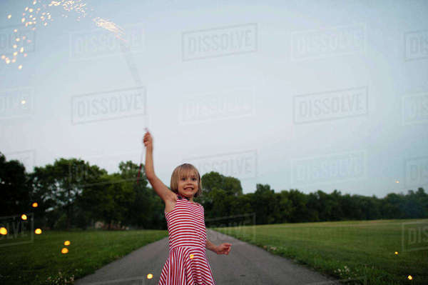 Happy girl holding firework while standing on road amidst grassy field at park Royalty-free stock photo