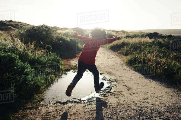 Rear view of boy with arms outstretched jumping over puddle on dirt road against clear sky Royalty-free stock photo