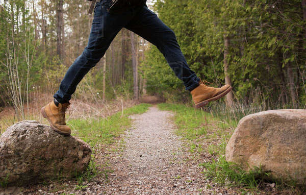 Low section of man jumping over rocks in forest Royalty-free stock photo