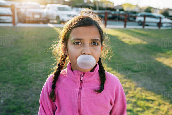 Portrait of girl blowing bubble gum while standing at park Royalty-free stock photo