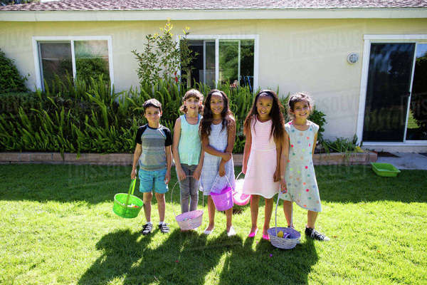 Portrait of happy friends and siblings holding Easter baskets at yard during sunny day Royalty-free stock photo