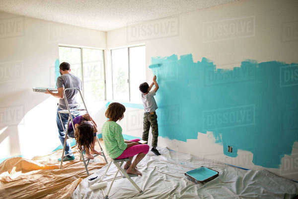 Father and son painting wall while sisters sitting on ladders at home Royalty-free stock photo