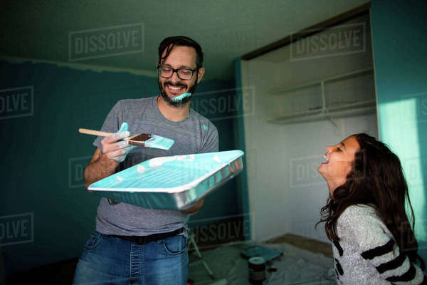 Happy father holding paint tray and brush while daughter laughing at home Royalty-free stock photo