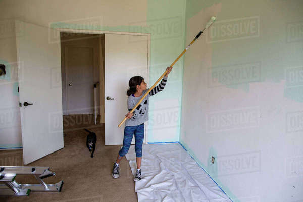 Girl painting wall using paint roller at home Royalty-free stock photo