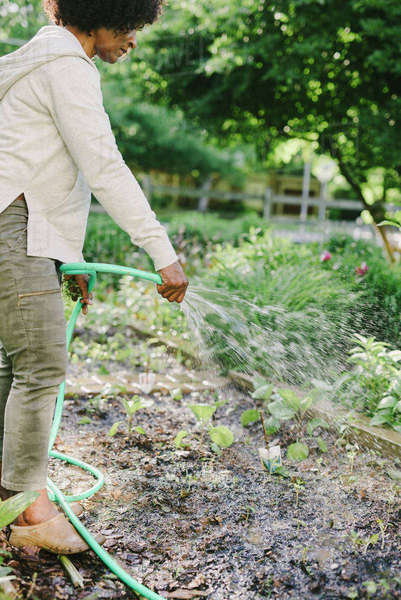 Side view of woman watering plants in yard Royalty-free stock photo