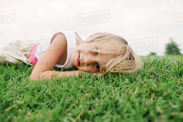 Portrait of cute girl lying on grassy field against clear sky Royalty-free stock photo