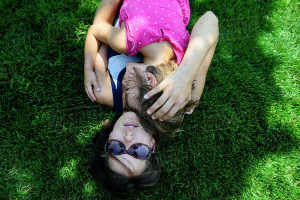 Overhead view of mother embracing daughter while lying on grassy field Royalty-free stock photo
