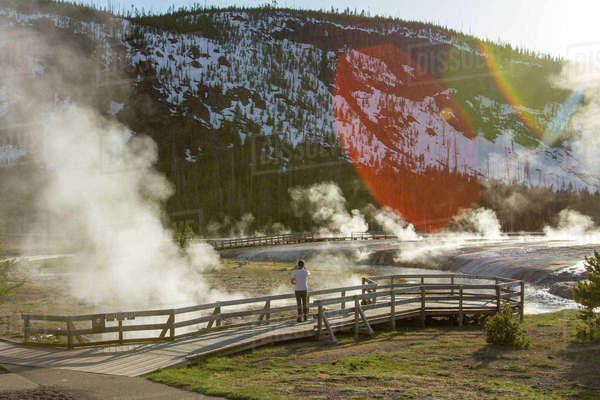 Mid distance of hiker looking at steam coming out from hot spring at Yellowstone National Park Royalty-free stock photo