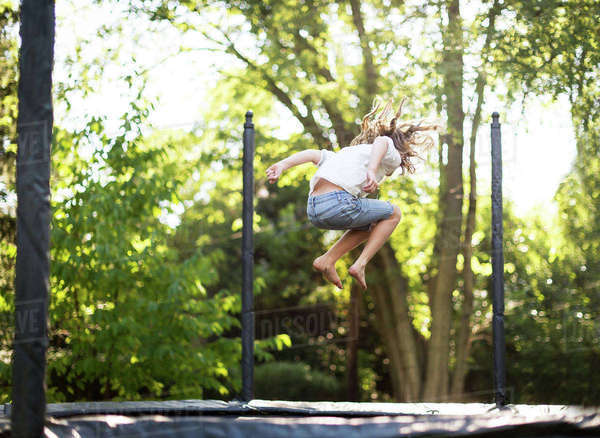 Full length of girl jumping on trampoline at park Royalty-free stock photo
