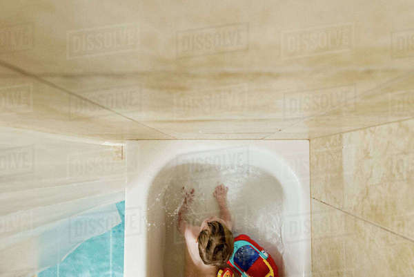 Overhead view of boy playing with toys in bath tub Royalty-free stock photo