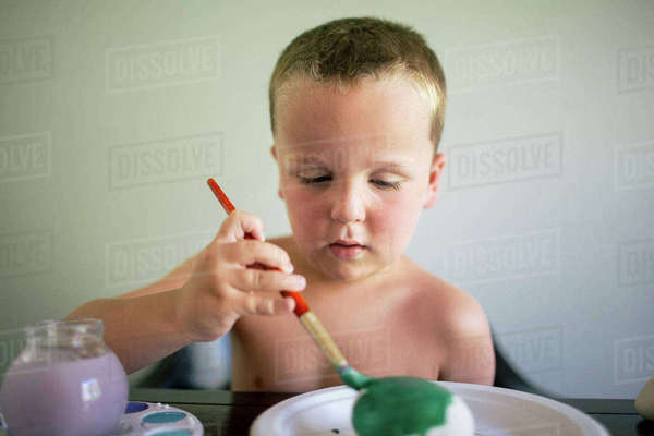 Shirtless boy coloring egg while sitting by table at home Royalty-free stock photo