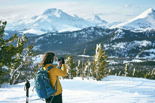 Rear view of female hiker photographing snowcapped mountains Royalty-free stock photo