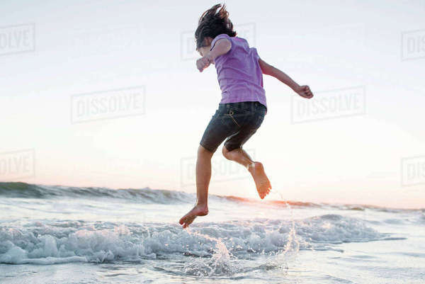 Low angle view of girl jumping on waves at beach against clear sky during sunset Royalty-free stock photo