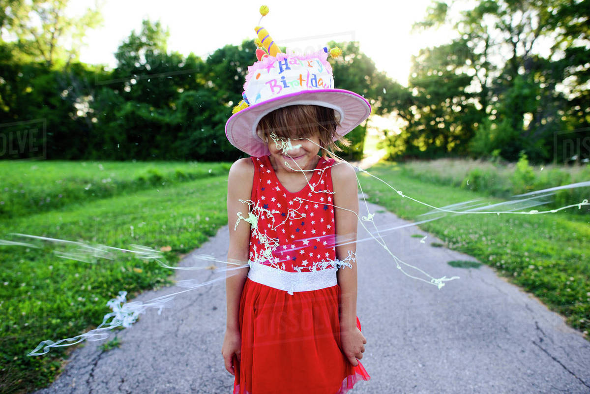 Girl In Birthday Cake Hat Standing On Road While Party Strings