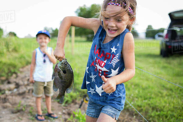 Playful sister with caught fish while brother standing in background Royalty-free stock photo