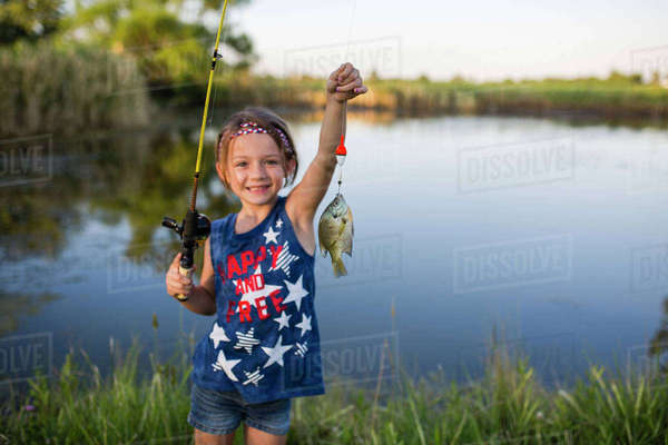 Portrait of girl showing off caught fish while standing against lake Royalty-free stock photo